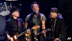 FILE - Bruce Springsteen, center, performs with Nils Lofgren, left, and Steven Van Zandt of the E Street Band during their concert at the Los Angeles Sports Arena in Los Angeles, March 15, 2016. The band's Sept. 7 concert in Philadelphia topped four hours.