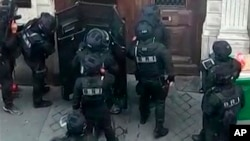 In this UGC image made from a mobile phone, police in riot gear surrounded the entrance of a building in central Paris where a man is believed to be holding two people hostage, in Paris, June 12, 2018.