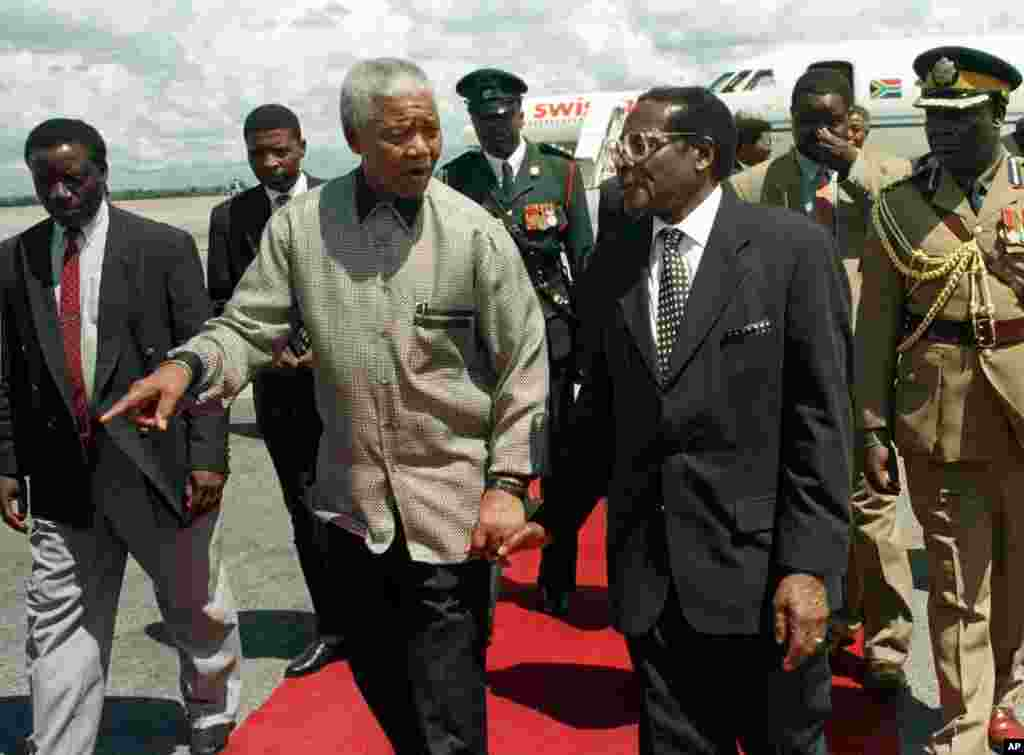 President Nelson Mandela, left, walks hand in hand with Zimbabwean President Robert Mugabe after the South African leader's arrival in Harare to address the 8th Assembly of the World Council of Churches, December 13, 1998. (AP)