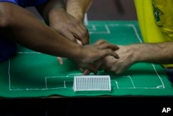 Carlos Junior, left, experiences the World Cup match between Brazil and Mexico with the help of an interpreter who uses tactile signing and a model soccer field to recount the game.