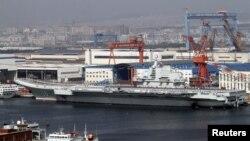 """Para tentara angkatan laut Tiongkok terlihat berdiri di atas geladak kapal induk pertama Tiongkok """"Lioning"""" yang berlabuh di pelabuhan Dahlian, propinsi Liaoning, bagian timur laut Tiongkok (25/9)."""