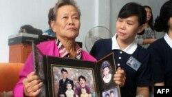 Bà Suharni, người Indonesia, cầm chân dung con trai và vợ, cả hai đều có mặt trên chuyến bay Malaysia bị mất tích, ngày 10/3/2014.