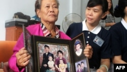 Grieving Indonesian mother Suharni displays a portrait of her son Sugianto Lo and wife Vinny Chynthya who are both passengers of the missing Malaysia Airlines flight, March 10, 2013.