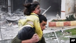 一名敘利亞人背著他的妹妹﹐在敘利亞政府軍空襲阿勒頗時街上逃避。