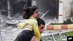 3일 시리아 알레포 지역에 정부군의 폭격 후, 부상당한 동생을 실어나르는 청년.