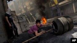 Seorang warga Palestina bersiap hendak membakar ban dalam bentrokan melawan pasukan Israel (tidak dalam gambar) di Hebron, Tepi Barat (3/4). Israel untuk pertama kalinya membalas tembakan roket Gaza sejak gencatan senjata tidak resmi, November lalu.