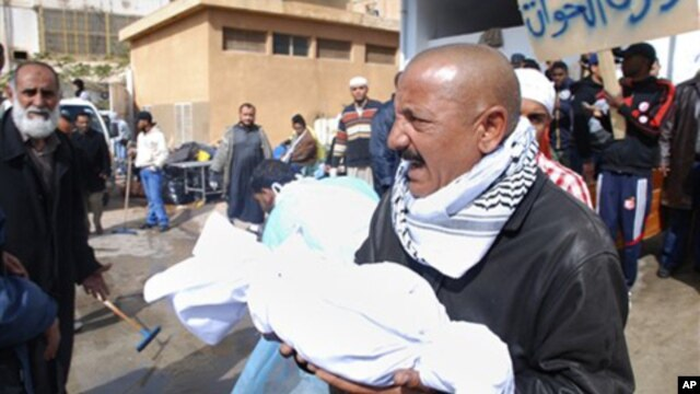 A Libyan man carries away partial remains of a man's body at Al-Jalaa hospital in Benghazi, February 21, 2011