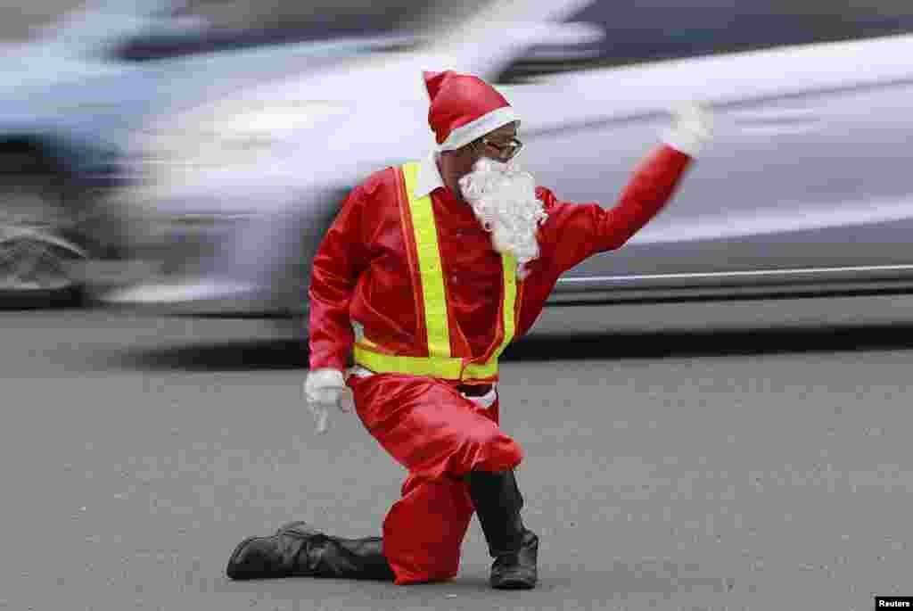 មន្រ្តីចរាចរណ៍ម្នាក់ឈ្មោះ Ramiro Hinojas ស្លៀកពាក់ជា Santa Claus ហើយបញ្ជាចរាចរណ៍នៅកន្លែងមមាញឹកមួយនៅក្នុងក្រុង Pasay ប្រទេសហ្វីលីពីន កាលពីថ្ងៃទី១២ ខែធ្នូ ឆ្នាំ២០១៥។