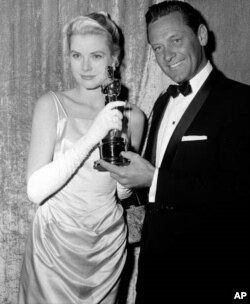 Best actress Grace Kelly receives her Oscar from the hands of presenter William Holden, on March 30, 1955, at the Pantages Theater in Hollywood, California.