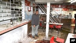 Pub-owner Charles Mwaura observes the bloodstained floor at the scene of a suspected grenade blast at his pub in downtown Nairobi, Kenya, October 24, 2011.