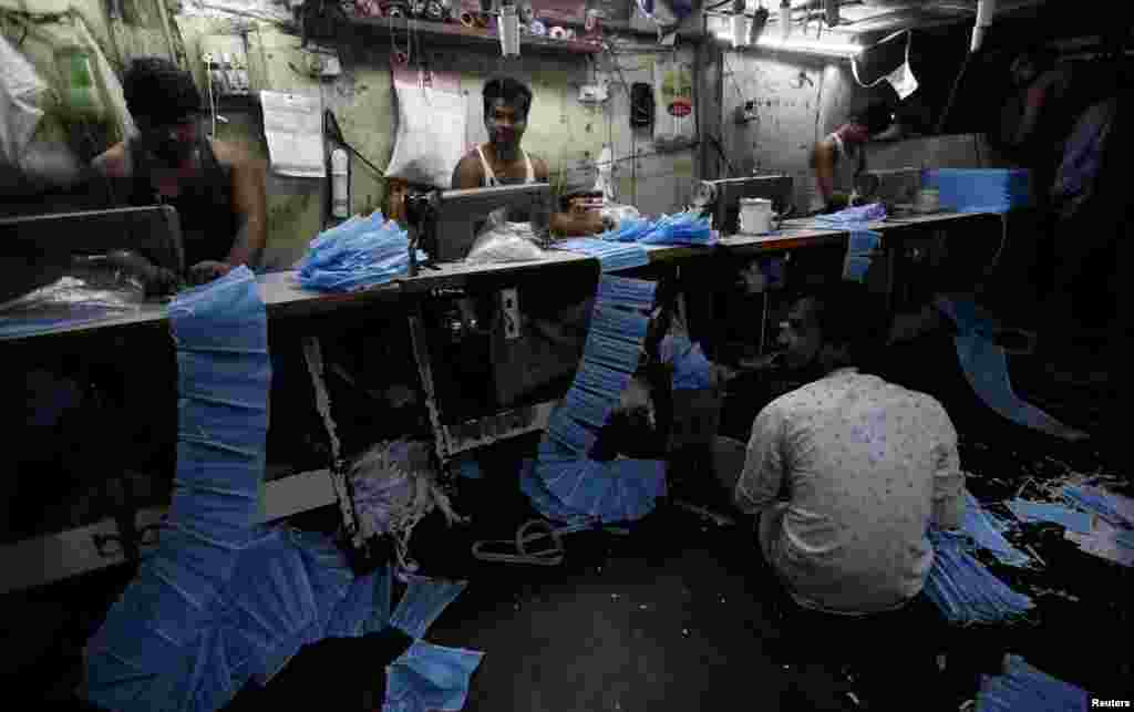 Workers make protective masks inside a workshop in Mumbai, India, March 14, 2020.