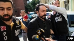 """Turkish police officers escort televangelist and leader of a sect, Adnan Oktar (C) on July 11, 2018, in Istanbul, as he is arrested on fraud charges. Turkish police detained the televangelist on fraud charges on July 11, 2018, notorious for propagating conservative views while surrounded by scantily-clad women he refers to as his """"kittens""""."""