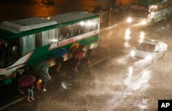 Commuters brave the rain and strong winds brought about by Typhoon Mangkhut, which barreled into northeastern Philippines before dawn, Sept. 15, 2018, in Manila, Philippines.