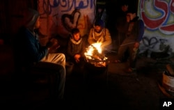 FILE - Palestinians, who get only several hours of electricity a day, sit around a fire outside their home in Gaza City, Jan. 25, 2016.