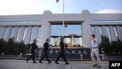 Cảnh sát tuần phòng trước cổng tòa án, và với an ninh võ trang bên trong phòng, nơi vụ xử án đang diễn ra, 12/9/14