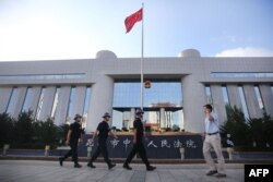 FILE - Police patrol at the gate of Kunming's Intermediate Court in Kunming, southwest China's Yunnan province.