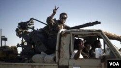 Seorang anggota pasukan pemberontak Libya mengacungkan tanda kemenangan saat mengepung kota Bin Jawad.