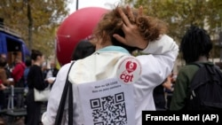 """A medical worker wearing a paper reading """"No to QR code, No to Health Pass, the vaccine does not prevent for the virus transmission, Freedom to choose to be vaccinated"""" during a protest gathering outside the Health Ministry in Paris, Sept. 14, 2021. (AP Photo/Francois Mori)"""
