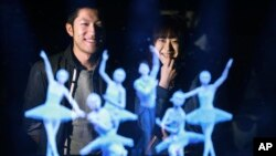 Tomoaki Ishizuka, left, and Yurika Yonekura watch the hologram of Japanese skater Yuzuru Hanyu, center, with ballet dancers with their scanned faces attached at newly opened Hologram Dance Theater at Madame Tussauds in Tokyo, April 28, 2016.