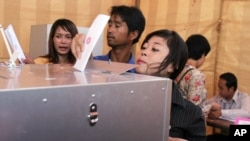 An unidentified Cambodian woman sticks out her head as she tries to cast her ballot at a polling station in Phnom Penh, file photo.