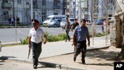 FILE - Police officers secure an area in the capital of Tajikistan, Dushanbe, where several Interior Ministry officers were shot dead earlier on Sept. 4, 2015, in attacks reportedly mounted by groups led by disaffected deputy defense minister Abdukhalim Nazarzoda.