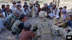 په دې تصویر کې د امریکايي پوځ یو عسکر په پکتیکا ولایت کې د افغان ژباړونکي ترڅنگ ځايي خلکو سره خبرې کوي