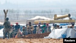 Binh sĩ Thổ Nhĩ Kỳ đứng gác trong lúc người Kurd từ thị trấn Kobani ở Syria chờ đợi phía sau hàng rào biên giới để vào thị trấn Suruc tị nạn.