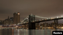 The Brooklyn Bridge is seen before the lights are turned off, in participation with Earth Hour, in New York March 31, 2012. Lights started going off around the world on Saturday in a show of support for renewable energy. REUTERS/Allison Joyce (UNITED STAT