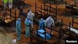 Relawan dan kerabat bersiap melakukan kremasi jenazah korban COVID-19 di desa Giddenahalli, pinggiran Bengaluru, India, 2 Mei 2021. (REUTERS/Samuel Rajkumar)