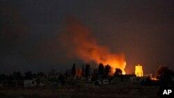 """Asap membumbung saat terjadinya bentrokan antara pemberontak dan pasukan setia President Bashar al-Assad memperebutkan markas militer """"Markas 17"""" di dekat kota Raqqa (20/11)."""