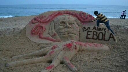 Nghệ sĩ Sudarshan Pattnaik cạnh tác phẩm bằng cát miêu tả bệnh dịch Ebola trên một bãi biển bang miền đông Odisha ở Ấn Độ.