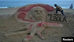 Seniman pasir Sudarshan Pattnaik membuat patung dengan pesan terkait Ebola di pantai di Puri, negara bagian Odisha di India timur (17/10).