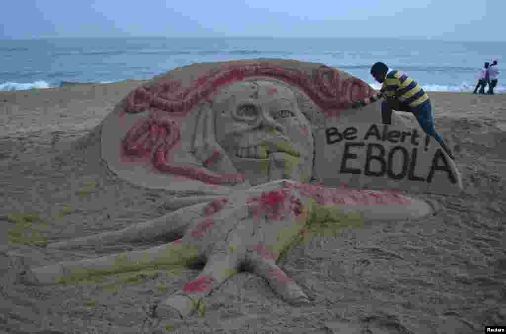 Indian sand artist Sudarshan Pattnaik works on a sand sculpture that shows a message about Ebola on a beach at Puri, in the eastern Indian state of Odisha.