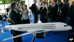 "FILE - People gather around a model of C Series Bombardier airplane on the eve of the Farnborough aerospace show, Farnborough, England, July 13, 2008. Boeing has accused Bombardier of receiving government subsidies that let it engage in ""predatory pricing."""