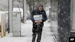 A person carries boxes as snow falls over the northern New Jersey region during a rare October snowstorm October 29, 2011.