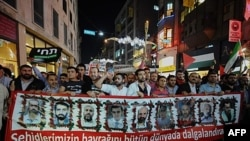 Các nhà hoạt động và những người ủng hộ Palestine cầm hinh các nạn nhân vụ đột kích tàu của Israel tuần hành đến quảng trưởng Taksim trong thành phố Istanbul, Thổ Nhĩ Kỳ