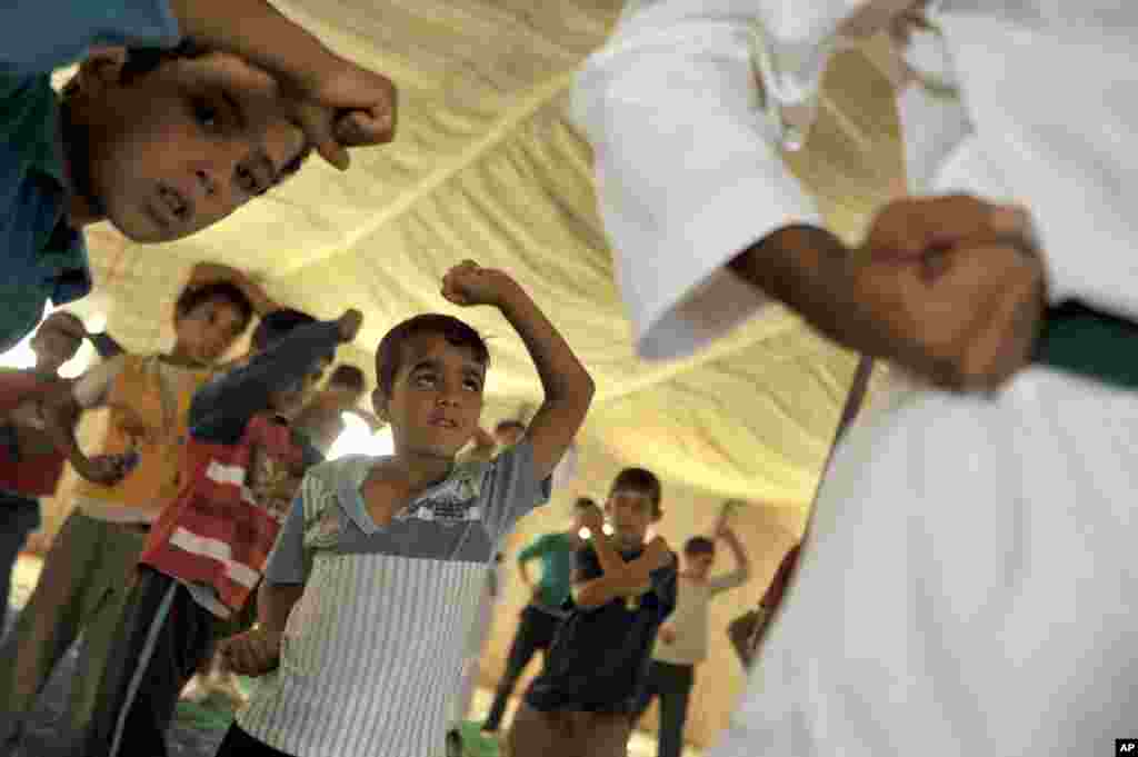 Syrian refugee children look at their Korean taekwondo instructor at Zaatari refugee camp near Mafraq, Jordan, Sept. 17, 2013.