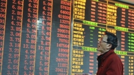 An investor looks at an electronic board showing stock information at a brokerage house in Hangzhou, Zhejiang province, China, December 14, 2012.