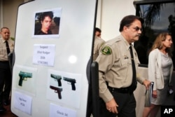 FILE- This May 24, 2014, photo shows Santa Barbara County Sheriff Bill Brown, right, after a news conference as he walks past a board showing photos of gunman Elliot Rodger and the weapons he used in a mass shooting the day before in Isla Vista, Calif. Authorities later concluded after an investigation that Rodger, who killed six people and injured 14 others, then killed himself, had acted alone.