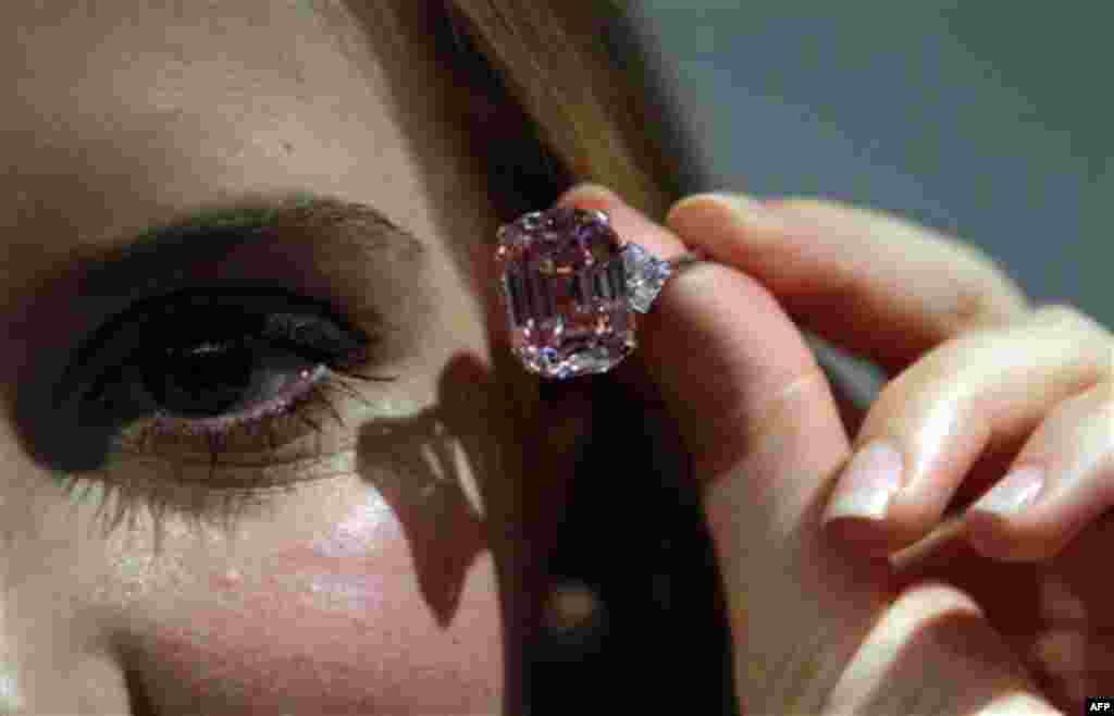 An employee of Sotheby's auction house holding a 24.78 carat fancy intense pink diamond mounted as a ring, that was last seen on the market some 60 years ago, ahead of an upcoming auction in central London. The rare emerald-cut pink diamond is estimated