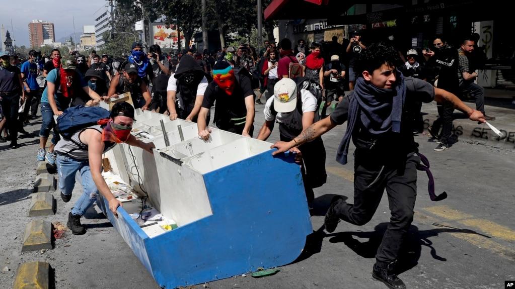 Manifestantes en Chile arrastran un mueble sacado de un negocio para usarlo como barricada en uno de los puntos de protesta en la capital. AP