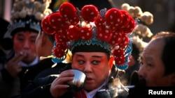 Seorang pemain drama mengenakan kostum tradisional sedang menikmati teh dan merokok dengan rekannya di sela persiapan mengikuti perayaan Tahun Baru China di Kuil Dongyue yang berusia , Beijing, 23 Januari 2012.