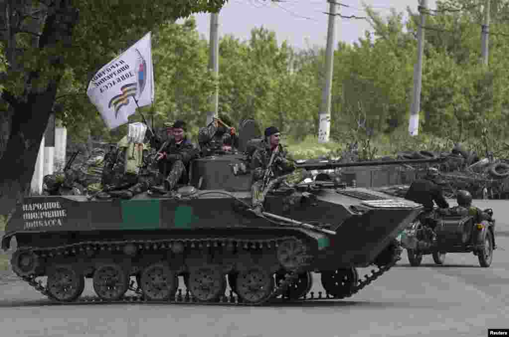 Pro-Russian armed men ride on top of an armored personnel carrier near Slovyansk, eastern Ukraine, May 5, 2014.