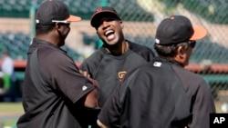 El expelotero Barry Bonds conversa con otros entrenadores durante una práctica de bateo con los Gigantes de San Francisco.