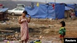 지난해 3월 중국과 접경지역인 미얀마 코캉의 난민캠프에서 한 여성이 머리를 감고 있는 모습을 어린 딸이 지켜보고 있다.