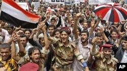 也門叛徒的武裝士兵和反政府示威者星期一高呼口號