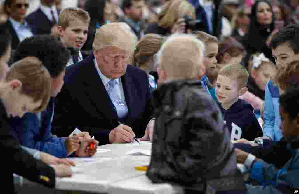 Presiden Donald Trump duduk bersama anak-anak menulis kartu-kartu ucapan untuk para prajurit di Gedung Putih, 2 April 2018, dalam acara tahunan Balap Telur Paskah.