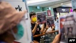 រូបឯកសារ៖ ប្រជាជនកាន់កាសែត Apple Daily ខណៈដែលពួកគេតវ៉ាប្រឆាំងឲ្យមានសេរីភាពសារព័ត៌មាន នៅក្នុងផ្សារទំនើបមួយក្នុងទីក្រុង ហុង កុង ថ្ងៃទី១១ ខែសីហា ឆ្នាំ២០២០។