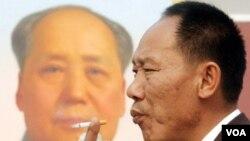 Un hombre camina al lado del otrora líder comunista Mao Zedong en Beijing.