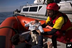 FILE - A 2-month-old baby from Libya is taken from a Libyan coast guard ship and loaded into a rubber rescue craft by members of the Spanish NGO Proactiva Open Arms, after being rescued from a wooden boat sailing out of control in the Mediterranean Sea.